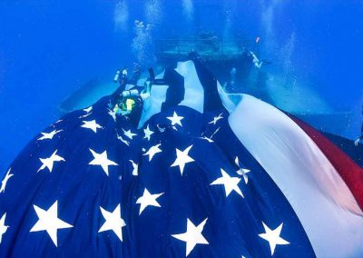 an American flag on the USNS Vandenberg waivers in the current with Key West Scuba Diving.