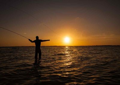 man casts fly rod into sunset with Key West Flats Fishing