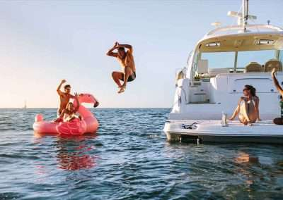 Friends jumping off a yacht rental with Key West Private Charter Boats