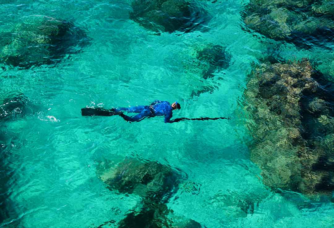 man swims in clear water with Key West Spearfishing